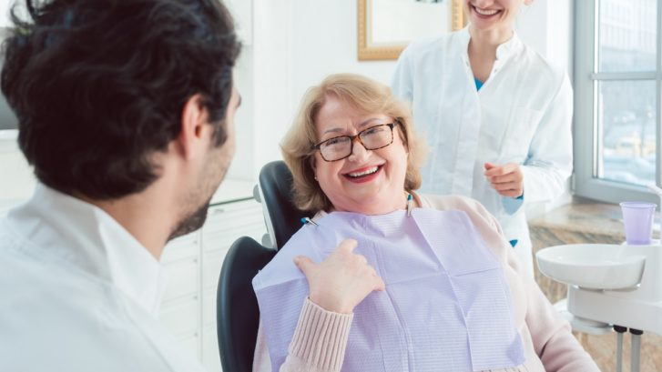 Dentist and assistant greeting senior patient