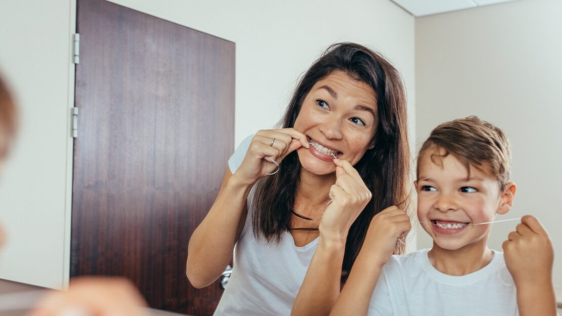 Mother and son cleaning teeth with dental floss