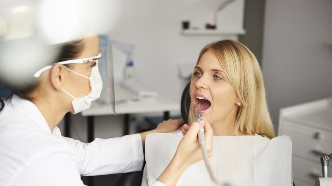Focused dentist with dental drill cleaning bad patient's teeth
